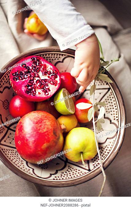 Close-up of child taking fruit from bowl