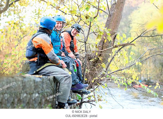 Male and female kayakers sitting on river bank wall laughing, River Dee, Llangollen, North Wales