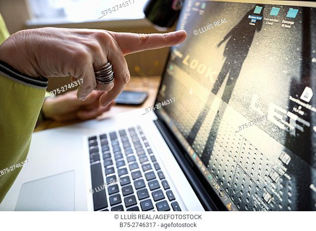View of woman's hands with ring, pointing at laptop computer screen