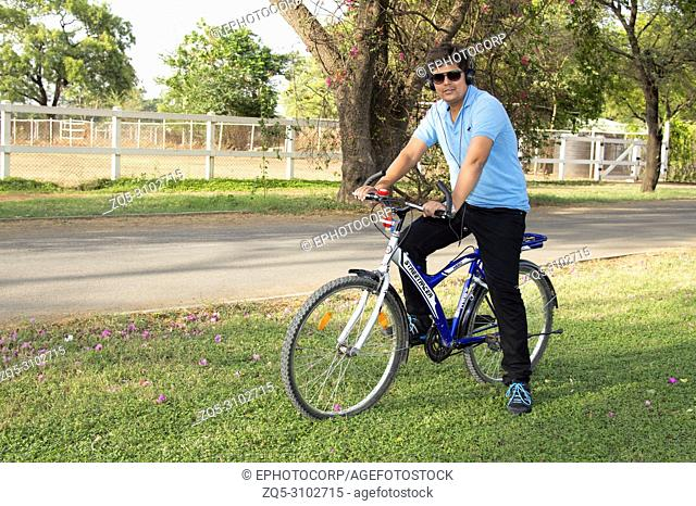 Young man wearing goggles riding bicycle and listening to music