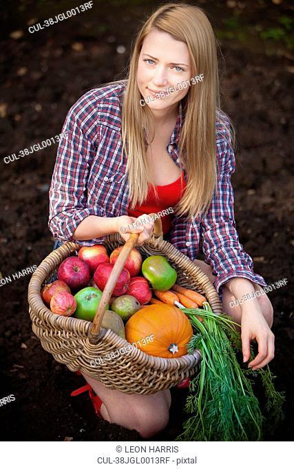 Woman gathering vegetables in garden