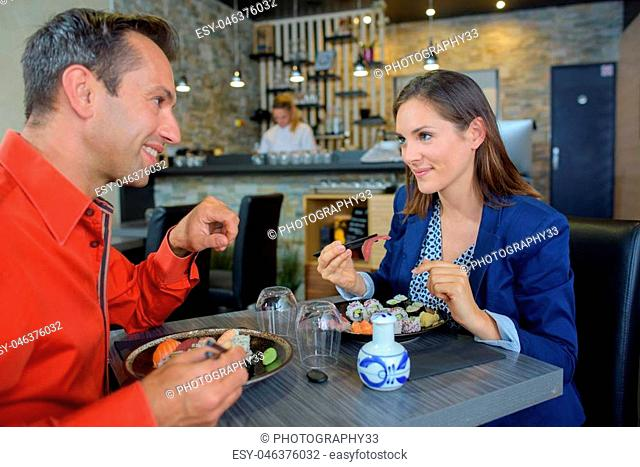 Couple eating sushi in restaurant