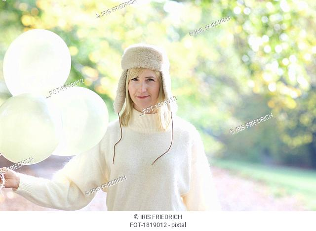 Portrait confident woman in white fur hat holding bunch of balloons in park
