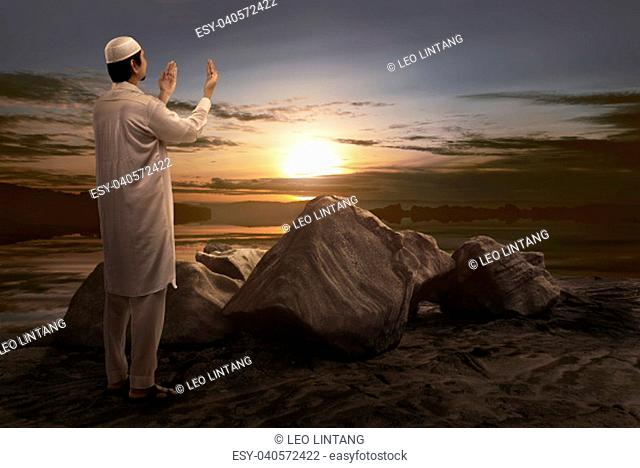 Young asian muslim man praying during sunset