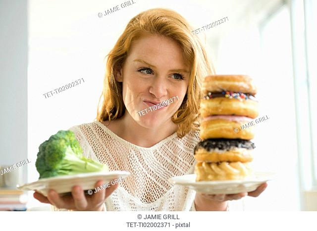 Young woman holding plate with donut and with broccoli