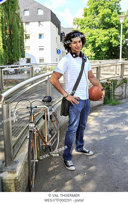 Young male student with basketball standing beside his racing cycle