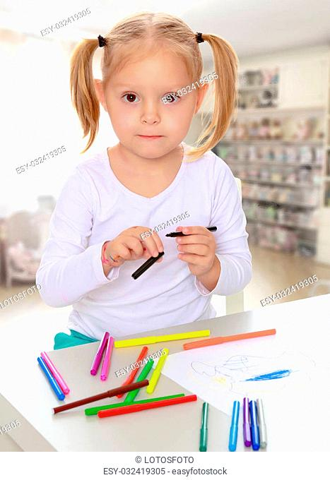 The concept of family happiness,and preschool education of the child , against a child's room with bookshelves.Pretty little blonde girl drawing with markers at...
