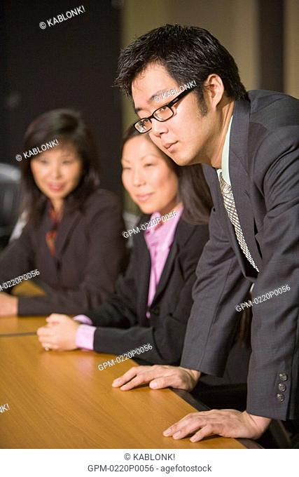Three Asian businesspeople sitting in boardroom, focus on man in foreground