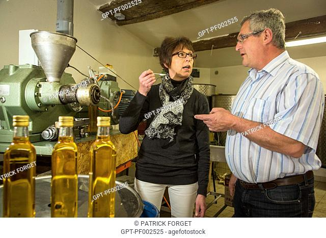 NATHALIE DE WEVER, SHOP OWNER AND MEMBER OF THE LOCAVORE MOVEMENT, TASTING THE OIL MADE BY JEAN-MARIE LENFANT, PRODUCER OF RAPESEED AND SUNFLOWER SEED OIL