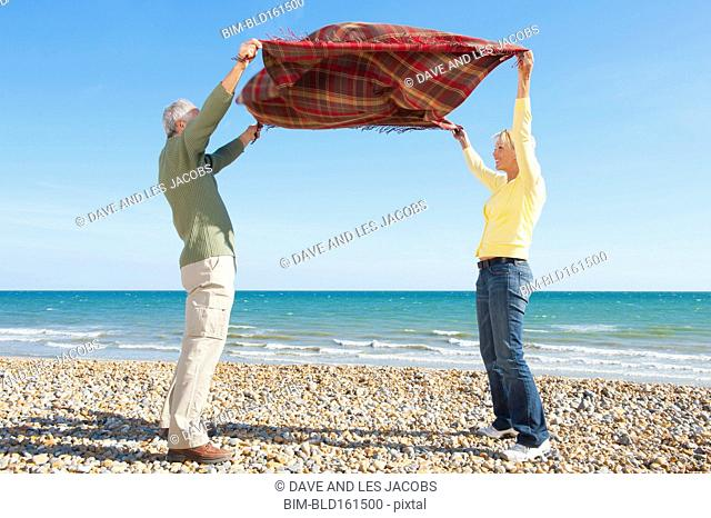 Caucasian couple spreading blanket on rocky beach