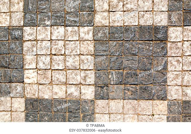 Stone pavement texture. Granite cobblestoned pavement background. Abstract background of old cobblestone pavement close-up