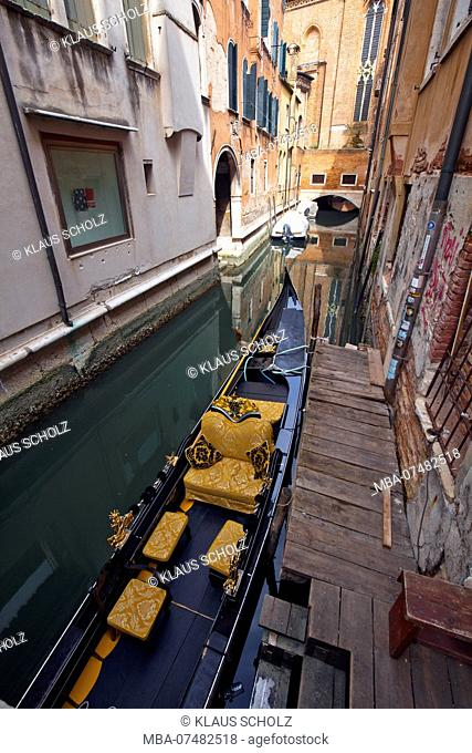 narrow canal with gondola between houses in Venice
