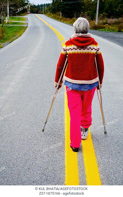 A woman on crutches with an injured foot surveys the long road ahead, Nova Scotia, Canada