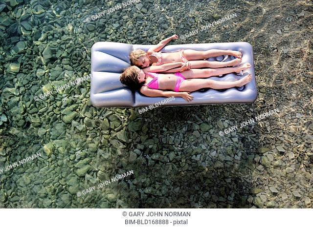 Caucasian girls floating on raft in lake