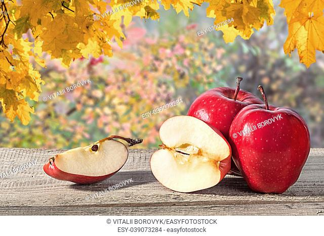 Several apples on a wooden table. Blurred background. Half and a quarter of an apple