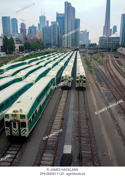 Several Go Trains resting with the Toronto skyline in the background. Toronto, Ontario, Canada