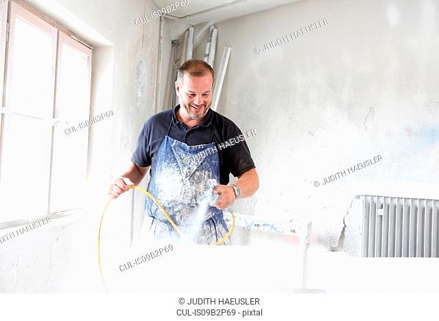 Man spray painting timber