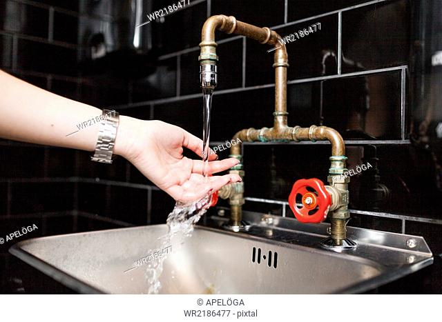 Cropped image of woman washing hands in sink at cafe washroom
