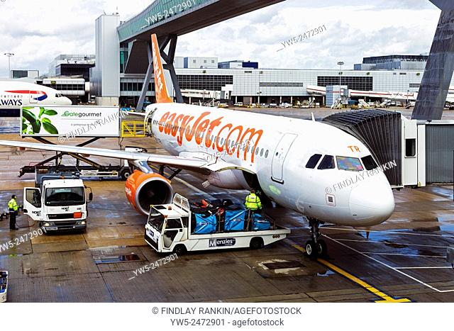 Easyjet plane being loaded with luggage at Gatwick airport, London, England, UK
