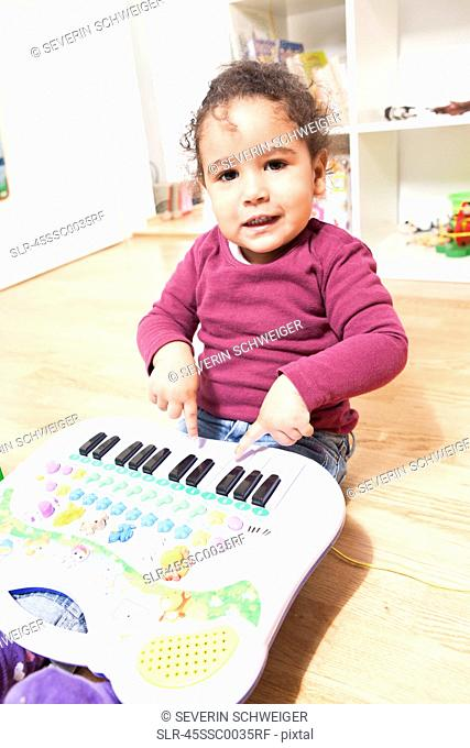 Girl playing with toy piano