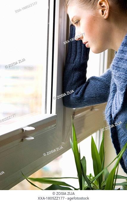 young woman looking by window