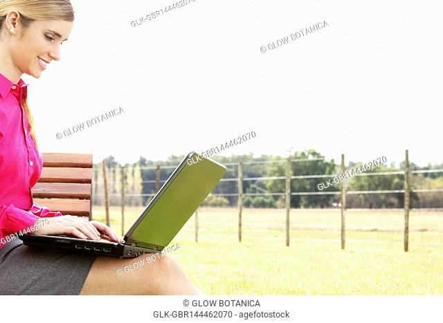 Businesswoman using a laptop in a park