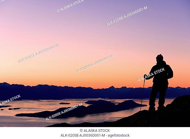 Male Hiker standing on ridge overlooking Lynn Canal & Berner's Bay near Juneau Alaska at sunset