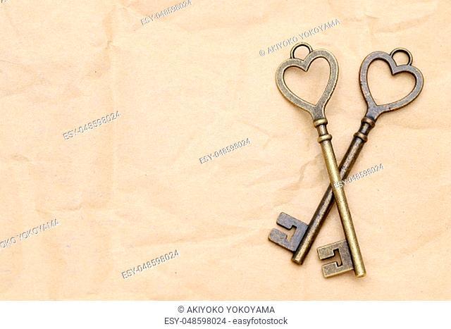 heart shaped vintage golden key on brown paper background