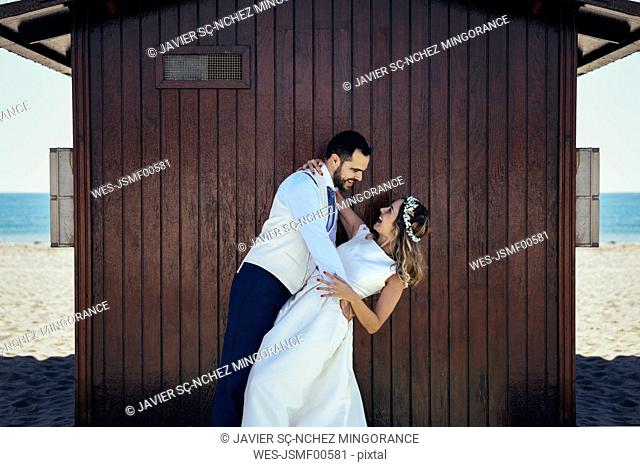 Bridal couple enjoying romantic moments in front of a beach hut