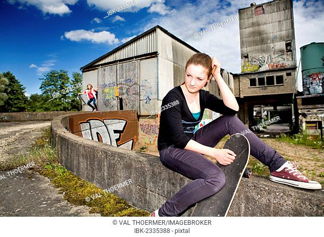 Portrait of a young teenage girl with a skateboard sitting in an urban area