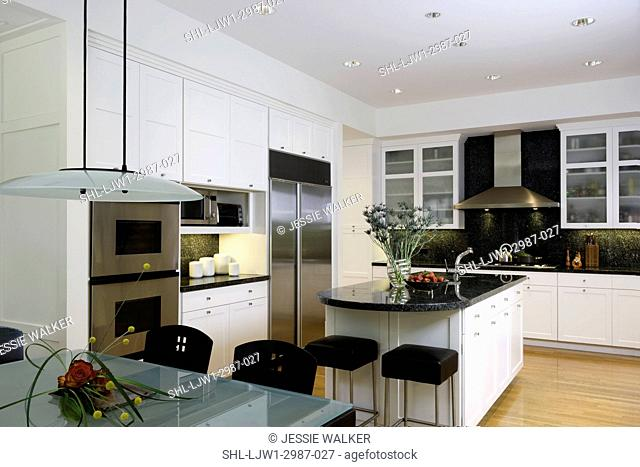 KITCHEN: horizontal with frosted glass top table in foreground, kitchen island, dark green / black granite counters, stainless steel appliances