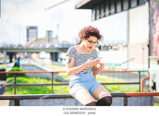 Woman sitting in urban area texting on smartphone, Milan, Italy