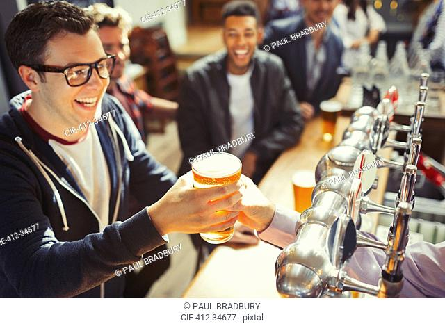 Smiling man receiving beer from bartender at bar