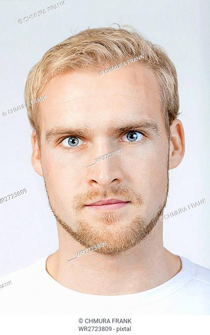 portrait of a young man with blond hair standing- isolated on light gray