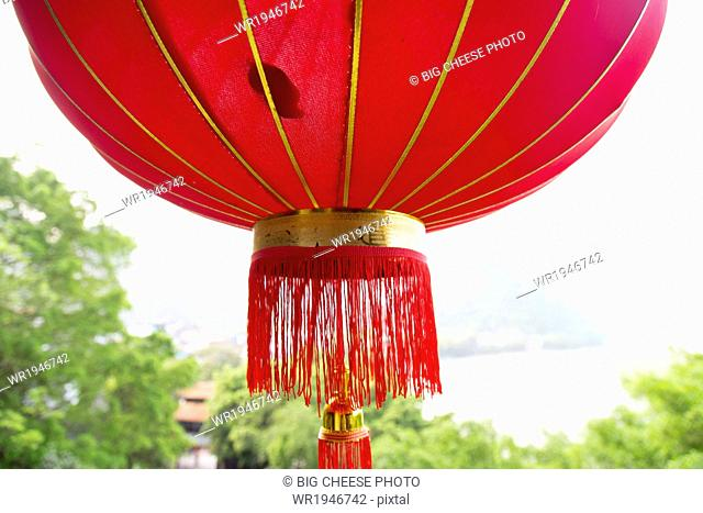Red lantern hanging in front of the Li River, Yangshuo, China