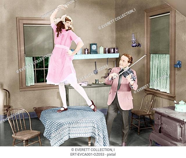 Man playing violin for woman dancing on table Old Visuals