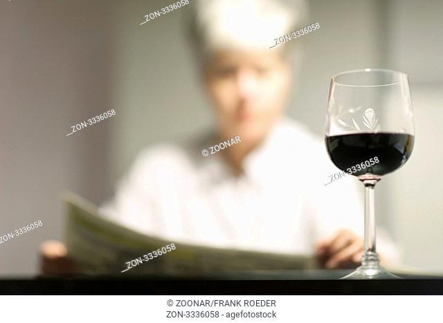 Lesende Frau mit einem Glas Wein sitzt an einem Tisch