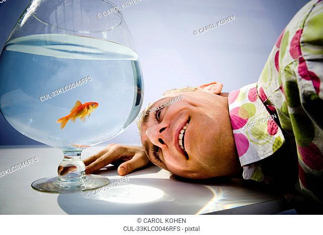 Man admiring goldfish in bowl