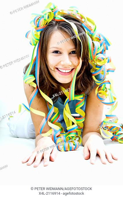Young woman in the midst of paper streamers (model-released)