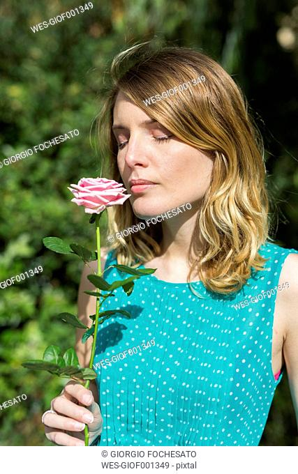 Portrait of young woman smelling rose blossom