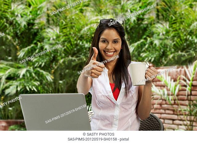 Woman drinking coffee, using a laptop and showing a thumbs up sign