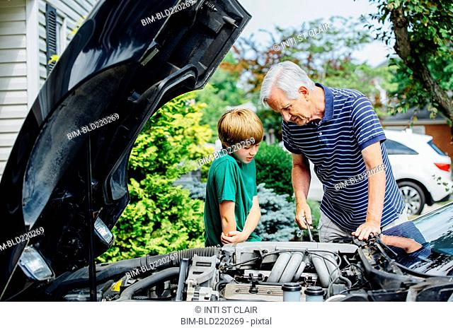 Caucasian grandfather and grandson working on car in driveway