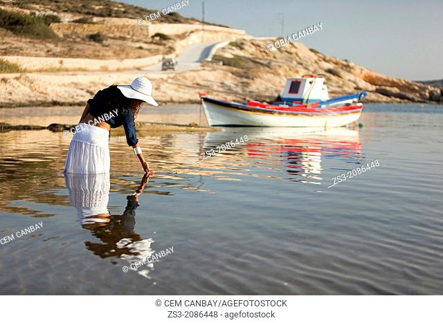 Woman playing with the water in the sea, Koufonissi, Cyclades Islands, Greek Islands, Greece, Europe
