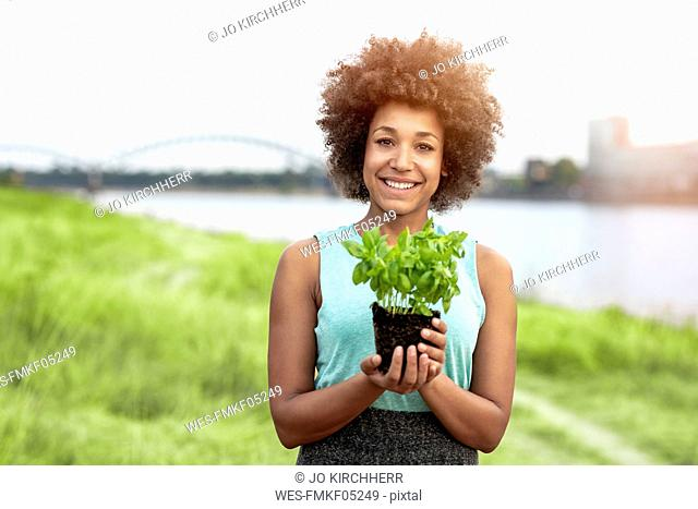 Portrait of smiling woman holding plant outdoors