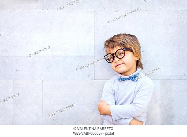 Portrait of smiling little boy wearingbow and oversized spectacles