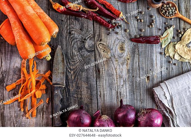 Fresh vegetables carrots and onions on a wooden surface, empty space in the middle
