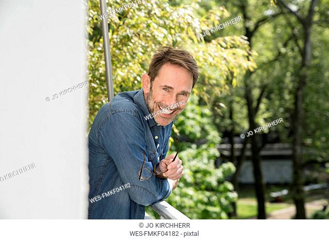 Portrait of laughing man on balcony