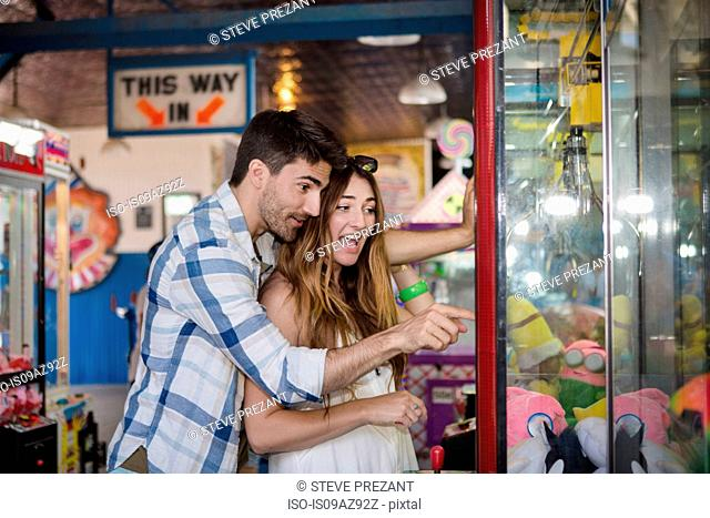 Couple at amusement park using arcade grabber, Coney island, Brooklyn, New York, USA