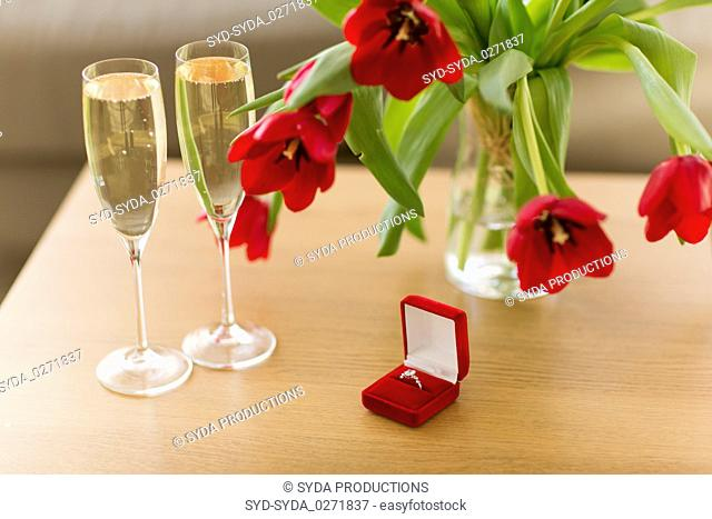 diamond ring, champagne and flowers on table