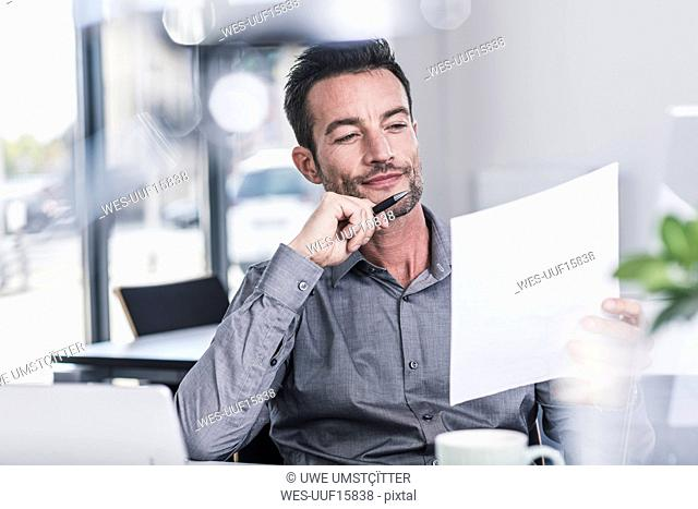 Businessman sitting in office, reading a letter